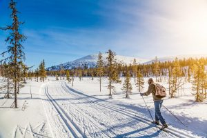 A-man-skiing-towards-hill-in-lapland